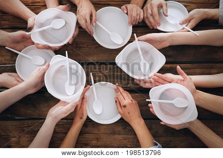 Hands of people with empty bowls at wooden table. Poverty concept