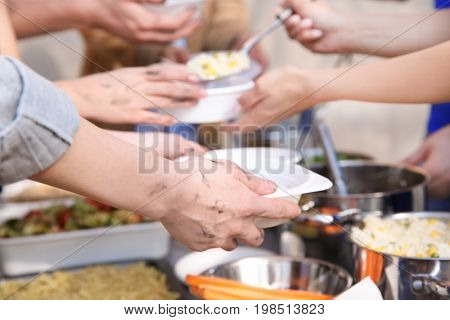Volunteers sharing food with poor people outdoors, closeup. Poverty concept