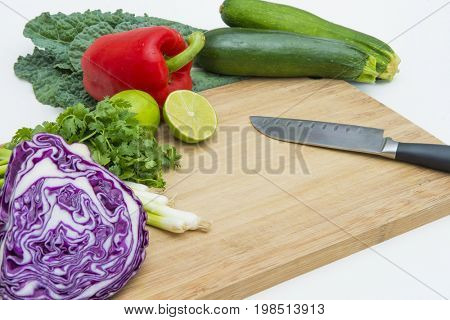 Food prep chopping slicing fresh healthy colorful vegetables produce cutting board knife on white background