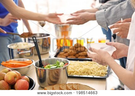 Volunteers giving food to poor people. Poverty concept