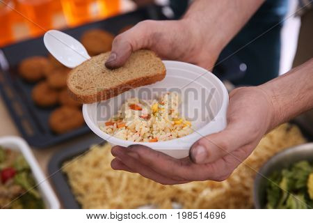 Hands of poor man holding bowl with rice and bread. Poverty concept