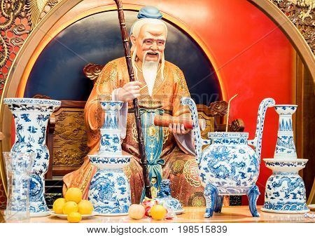 Shanghai, China - Nov 6, 2016: Inside the 600-year-old Old City God Temple. Figurine of an ancient Taoist deity on altar. Low-light image.