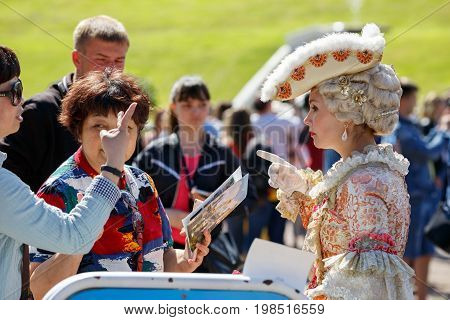 PETERHOF/ RUSSIA - JULY 2, 2017. Asian tourists want to be photographed with the model in an ancient court costume in the Peterhof park. Saint Petersburg, Russia.