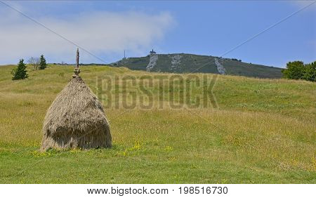The Matajur mountain in Friuli Venezia Giulia Italy. The rounded hill with the church in the background is the peak of the Matajur. A loose stacked haystack can be seen in the foreground