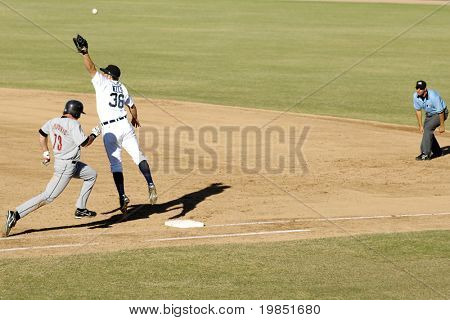 MESA, AZ - NOV 20: First baseman Casper Wells of the Mesa Solar Sox stretches as Brian Bogusevic of the Scottsdale Scorpions runs to first base the Arizona Fall League game on November 20, 2008.