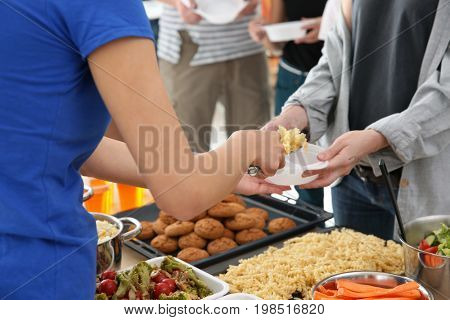 Volunteer sharing food with poor people. Poverty concept