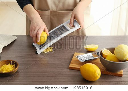 Female chef grating zest of lemon on kitchen table