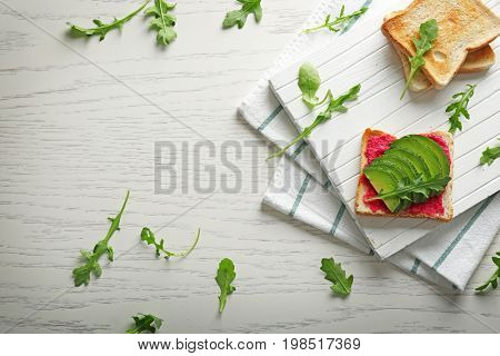 Delicious spicy toast with avocado and ruccola on white wooden table