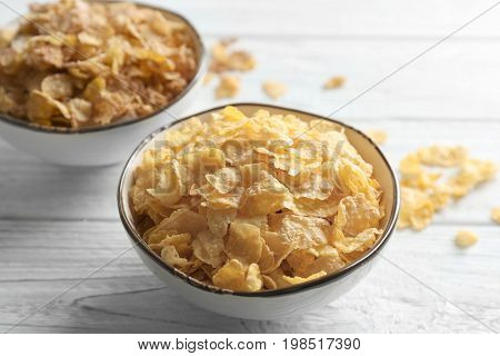Bowls with different healthy cornflakes on wooden background