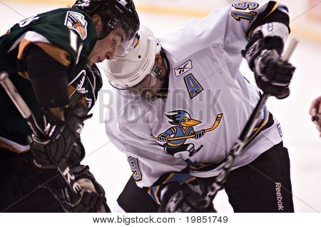 PHOENIX, AZ - DECEMBER 18: Phoenix Roadrunners center Kimbi Daniels (#19) and Utah Grizzlies wing Evan Kotsopoulos (#16) battle during the ECHL hockey game on December 18, 2008 in Phoenix, Arizona.