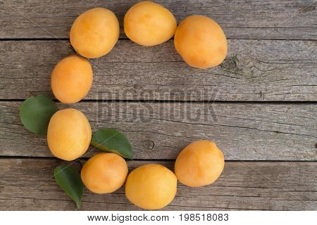Letter C made from apricots on a wooden background. Vitamin C concept.
