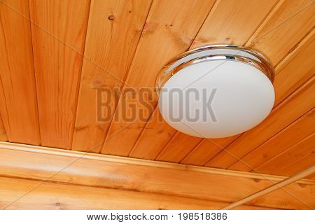 Ceiling glass white lamp on a wooden ceiling.