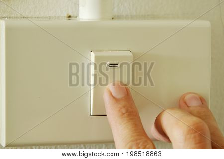 human finger closed toggle switch in plastic box on wall