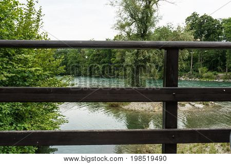 wooden handrail above river surrounded by trees