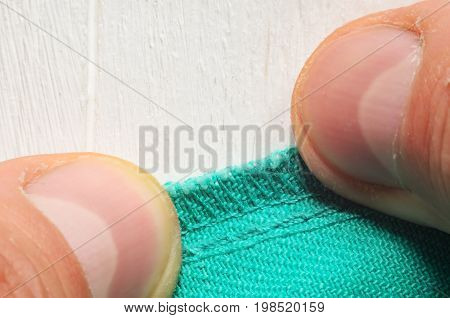 Inner seam on clothes pressed close to the table with hands. Close-up shot of a tailor at work
