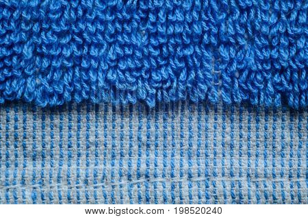 Macro shot of a blue towel. Texture is similar to the texture of a fleecy knotted-pile carpet. Geometric pattern of villi on fabric material. Towels edge finishing element