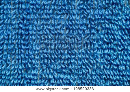 Macro shot of a blue towel. Texture is similar to the texture of a fleecy knotted-pile carpet. Geometric pattern of villi on fabric material