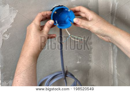 Electrical blue round plastic box is installed by hands close-up.