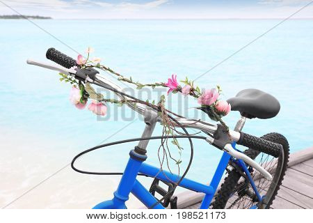 Modern bicycle with flower garland on sea beach