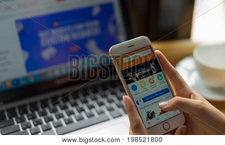 Singgapore. July, 2017:a Woman Is Typing On Alibaba.com Search Engine From Phone And Laptop; Alibaba