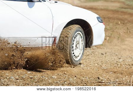 Rally car turning in dirt  track .