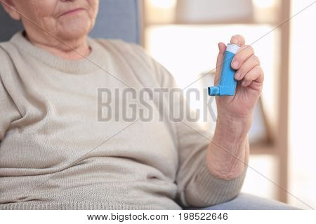 Elderly woman with inhaler for asthma at home