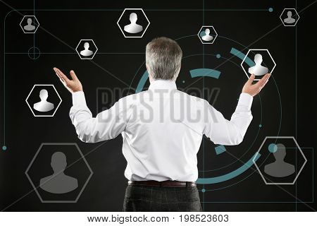 Senior man working with virtual screen on black background. Concept of human resources management
