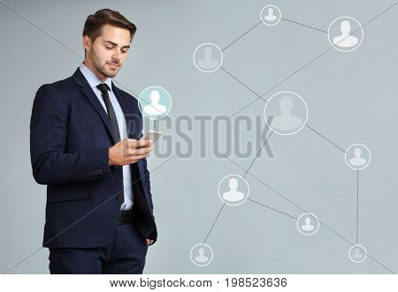 Young man using smartphone on light background. Concept of human resources management