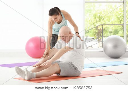 Instructor helping senior man to practice yoga in gym