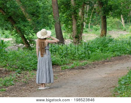 Beautiful girl in a hat and long hair is standing on a footpath in a green forest
