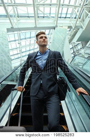 Businessman at the airport going down the escalator