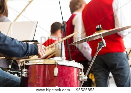 drum kit, jazz band music concept - closeup on hand of musician playing with stick on percussion instrument and ride cymbal, orchestra rehearsal before concert performance, selective focus