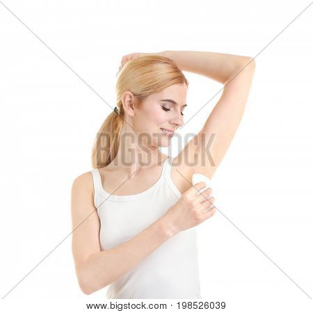 Beautiful young woman using deodorant on white background