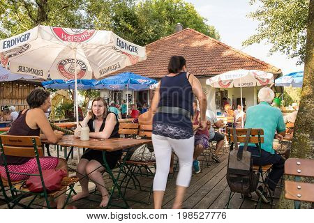 Kirchdorf am Inn-August 022017: People relax late in the afternoon in a beergarden enjoying conversations with friends