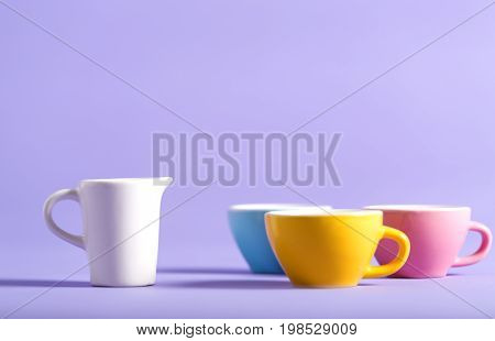 Little teacups and milk jar on a bright background