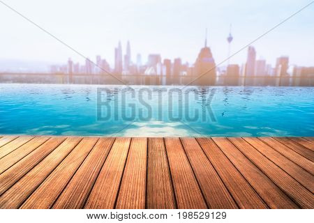 Empty wooden table with swiming pool on roof top city view background.- Can be used for display or montage your products.