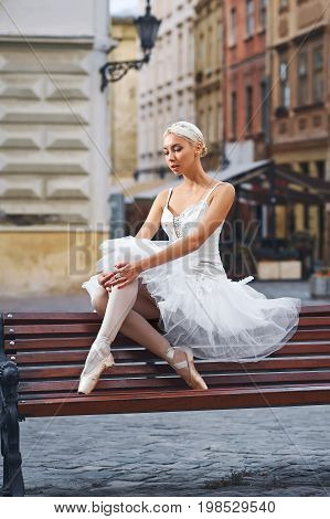 Vertical portrait of a graceful ballerina sitting alone on the bench in the city street grace elegance femininity sensuality loneliness art.
