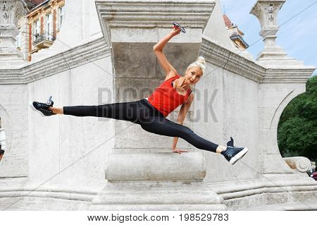 Horizontal shot of a beautiful female modern dancer performing on the city streets doing splits dancing ballet hip hop contemporary artistic performance flexibility concept.