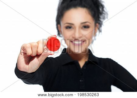 Beautiful young dark haired Hispanic woman smiling cheerfully holding out red casino token isolated on white.