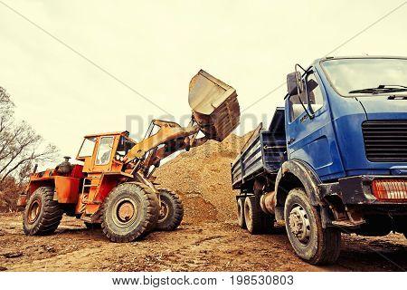 Excavator unloading sand in construction site, industry