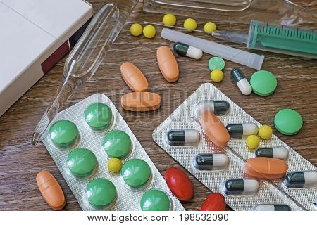 On the table are several types of pills and vials. Standing next to a glass of water for the use of the medications.