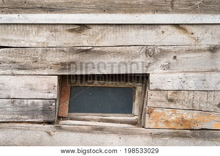 The little window of the old wooden log house on the background of wooden walls.