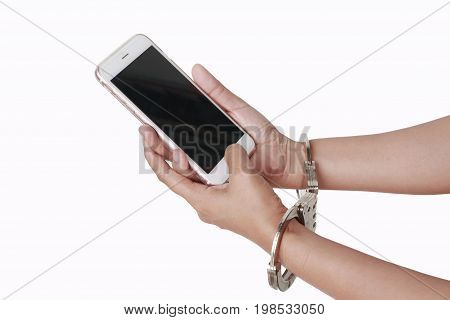 Female hand holding mobile phone with handcuffs.