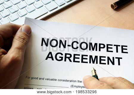 Man is signing Non compete agreement. Outsourcing concept.