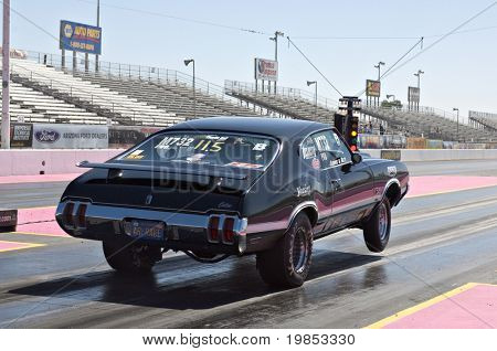 CHANDLER, AZ - OCTOBER 1: A hot rod car pops a wheelie at the start of the race at the NHRA Pacific Division drag racing championship on October 1, 2009 in Chandler, Arizona.