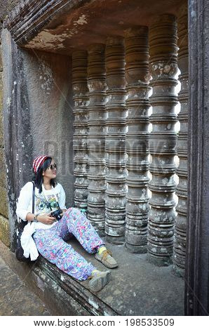 Thai Woman Sitting And Take Photo On Window Of Wat Phu Or Vat Phou