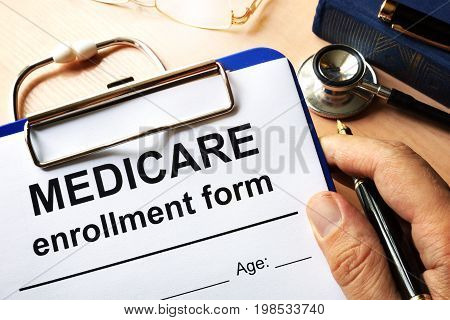 A Medicare enrollment form in a hand.