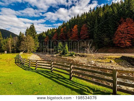 Fence On The Meadow Near Forest River In Autumn Mountains