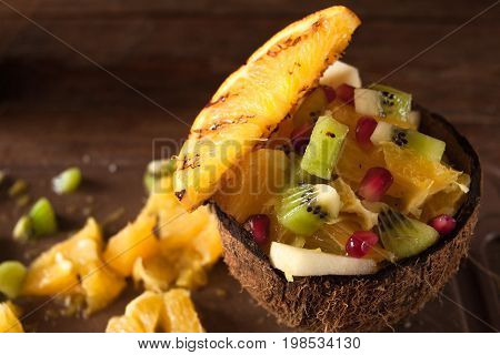 Exotic tropical fruit salad mixed in coconut shell. Orange, apple, kiwifruit pieces in nut bowl and pomegranate seeds decoration
