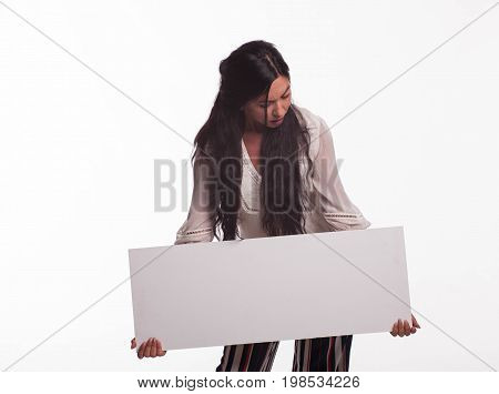 Young surprised woman portrait of a confident businesswoman showing presentation, pointing placard gray background. Ideal for banners, registration forms, presentation, landings, presenting concept.